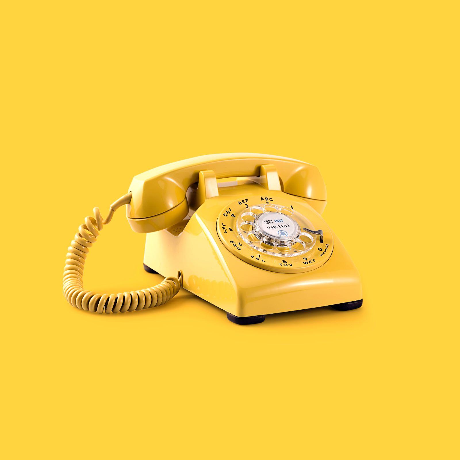 Ouderwetse gele telefoon op gele achtergrond